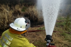 Crews working a ground monitor at a peat fire